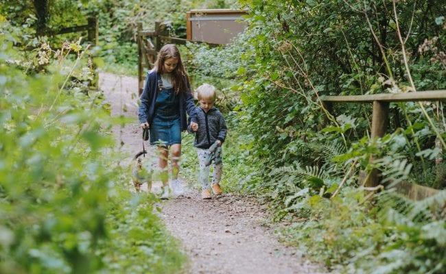 Children walk their dog through Hermitage Woods