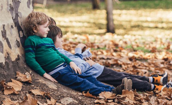 Devon in Autumn kids sitting near a tree in autumn leaves