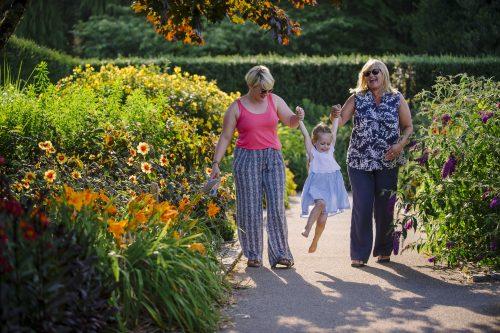 A family walk through the Hot Garden at a Summer Late Event at RHS Garden Rosemoor.