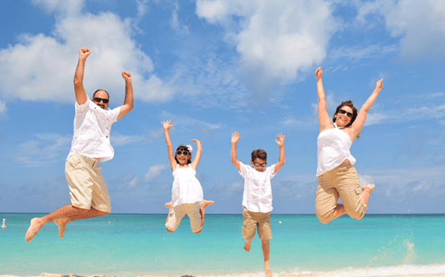 Family jumping in the air on a Devon beach